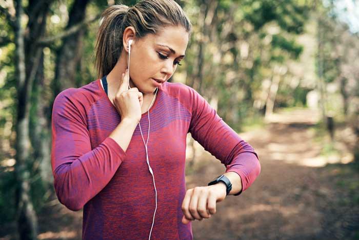 Κοπέλα μετρά τους καρδιακούς παλμούς της στην προπόνηση σε δάσος